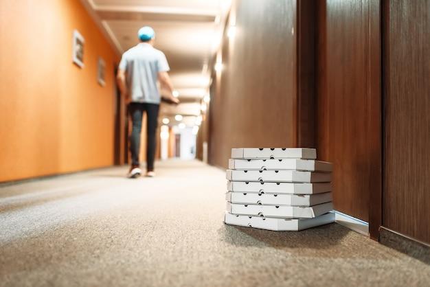 顧客のドアにピザが入ったカートンボックス、配達の少年が立ち去る