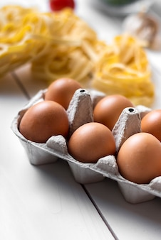 Carton of brown egg on wooden surface