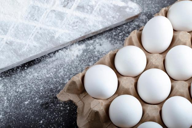 Картонный контейнер сырых яиц и пролитой муки на черной поверхности.
