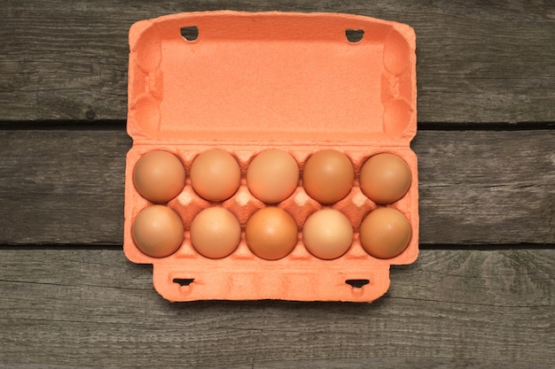 Carton of organic brown eggs on wooden board. top view.