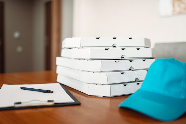 Carton pizza boxes, cap and empty order on table