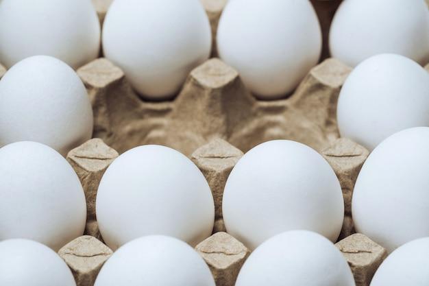 Картонный лоток с куриными белыми яйцами. пустые клетки в середине. крупный план. сельскохозяйственные продукты и натуральные яйца. здоровая пища.