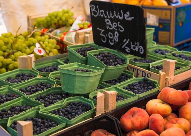 市場で健康的なジューシーな果実で満たされたカートン