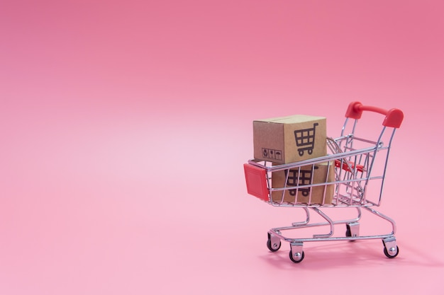 Cartons or paper boxes in blue shopping cart on pink