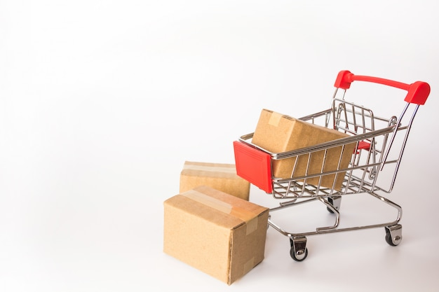 Cartons or paper boxes in red shopping cart on white background.