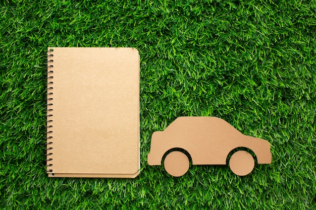 Cartoon car and notebook in grass