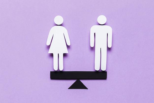 Мультфильм женщина и мужчина, стоя в балансе на качелях