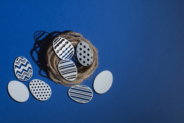 Carved easter paper eggs in a jute nest on a classic blue background, color 2020 classic blue pantone