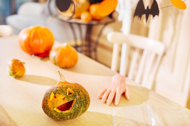 刻まれたカボチャ。ハロウィーンパーティーのための魔女の指のクッキーの近くのテーブルに横たわっている刻まれたハロウィーンのカボチャのクローズアップ