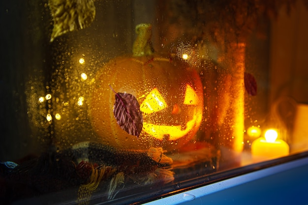 The carved pumpkin looks out the window. jack lantern, halloween concept. rainy, autumn. focus on glass.