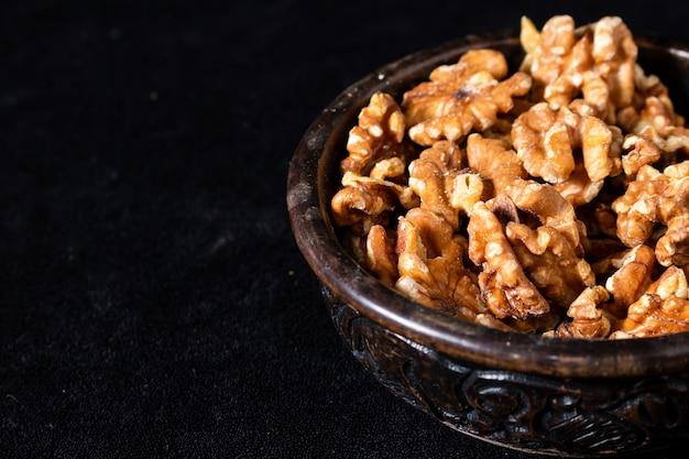 Резная деревянная чаша с очищенными семенами грецкого ореха на черном фоне. 45 град. посмотреть. крупный план, место для текста.