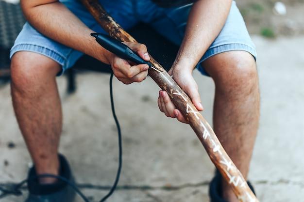 Carving diamond willow walking stick. man making runes on wooden stuff