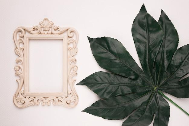 Carving rectangular wooden frame on green single leaf against backdrop