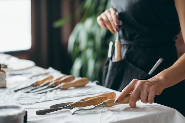 カービングツールの品揃え。テーブルの上に配置されたクラフトセット。ノミを選ぶエプロンの女性。