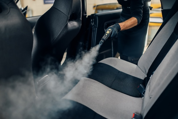 Carwash service, male worker in gloves cleans seats with steam cleaner. professional dry cleaning of car interior