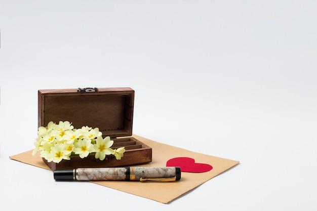 木製ヴィンテージcas、封筒、ペン、段ボールの赤いハート、白い背景に白い春の花。