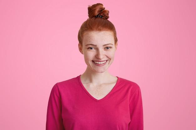 ピンクの壁を越えて分離されたお世辞を受け取って喜んでいる結び目で結ばれた赤い髪の幸せな笑みを浮かべてそばかすの女性。美しい女性は友人と屋外で散歩するつもりのcasaulの服を着ています