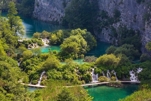 플리트 비체 호수 국립 공원 (크로아티아)의 호수를 가로 지르는 폭포와 널빤지 보도가있는 캐스케이드 깨끗한 호수