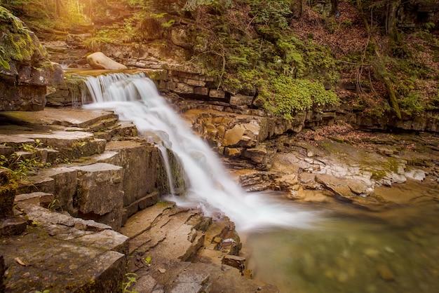 朝、葉から太陽光線が差し込むカスケードマウンテンの滝。長時間露光のため、水がぼやけています。