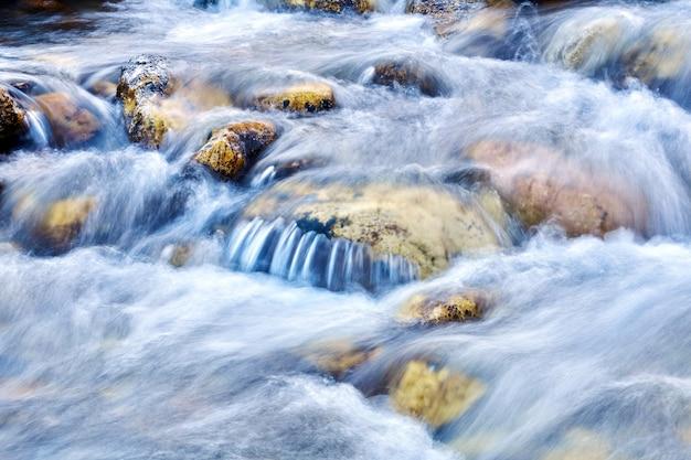 岩の間の山川の小さな滝のカスケード、水は動きでぼやけています