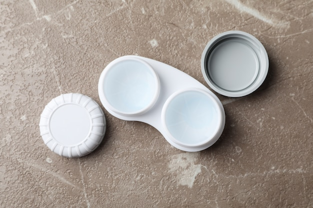 Case for contact lenses on grey table, top view
