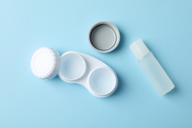 Case for contact lenses and liquid on blue surface, top view