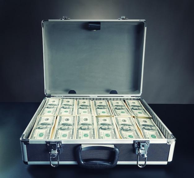 灰色の背景にお金でいっぱいのケース