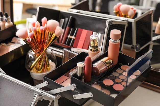 Case of professional makeup artist with decorative cosmetics on table