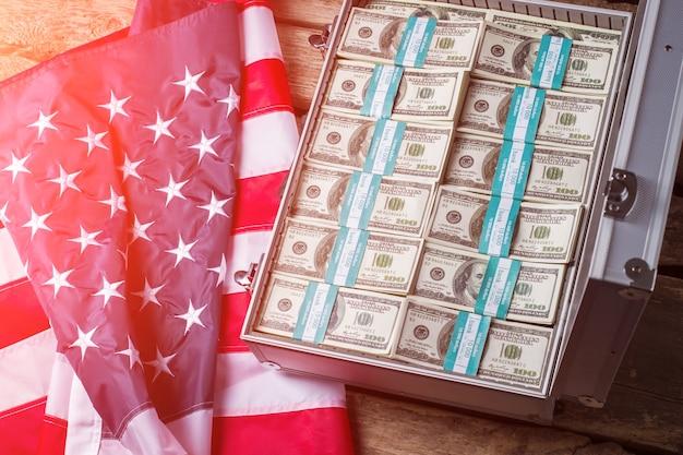 Футляр с долларами рядом с флагом. американский флаг, чемодан и деньги. загляните внутрь. страна дает хорошие шансы.
