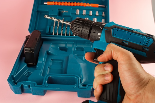 Case with a screwdriver and nozzles on a pink background