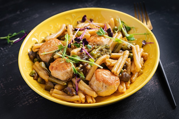 Caserecce pasta with meatballs in  sweet and sour sauce and vegetables in bowl