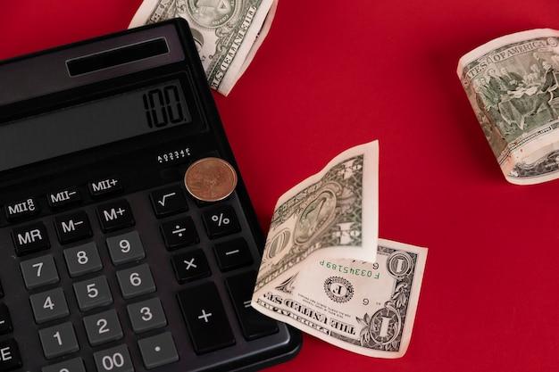 現金、電卓が赤い背景に散らばっています。スペースをコピーします。