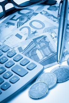 Cash, coins, pen, glasses and pocket calculator