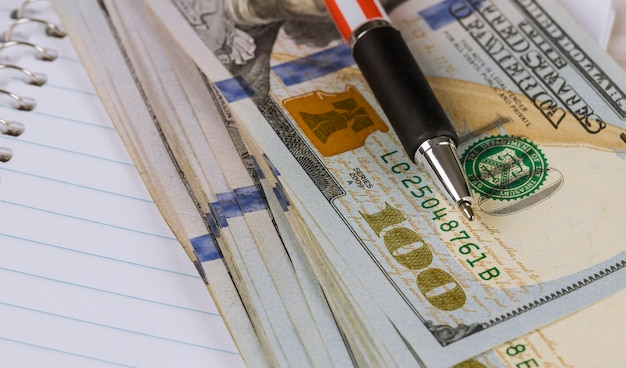 Cash money 100 us dollar banknotes and a pen
