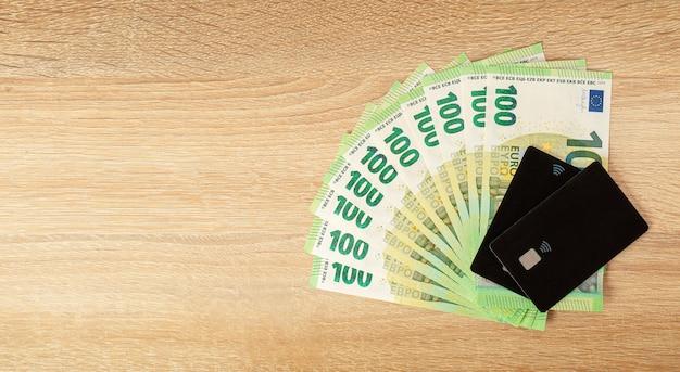現金対クレジットカード。木製の背景にユーロ通貨。