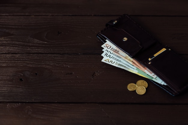 Cash in wallet. euro cash in brown wallet on wooden background