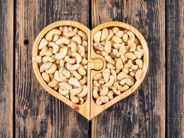 Cashew in a heart shaped wooden plate top view on a wooden table