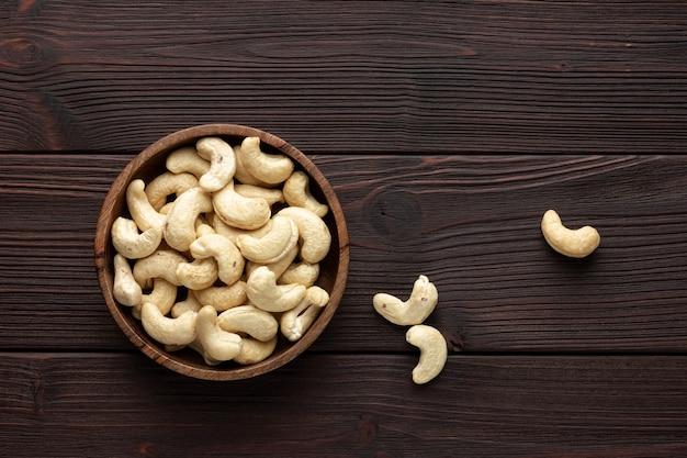 Кешью в деревянной миске. орехи на коричневом столе. здоровая закуска.
