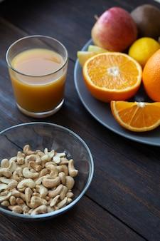 Орехи кешью и сок рядом с другими фруктами на черном деревянном столе