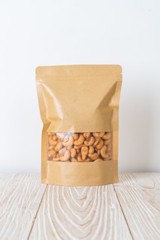 Cashew nuts in bag on wood surface