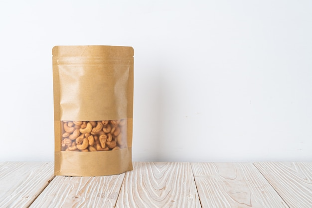 Cashew nuts in bag on wood table