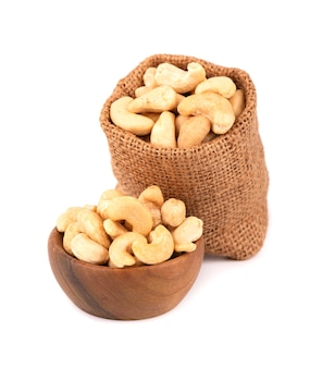 Cashew nuts in bag and wooden bowl, isolated on white background.