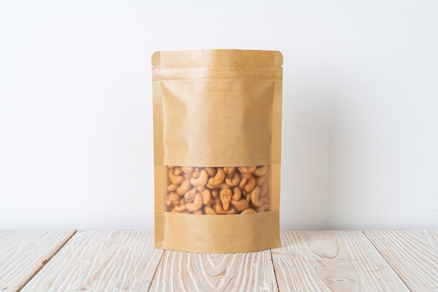 Cashew nuts in bag on wooden table