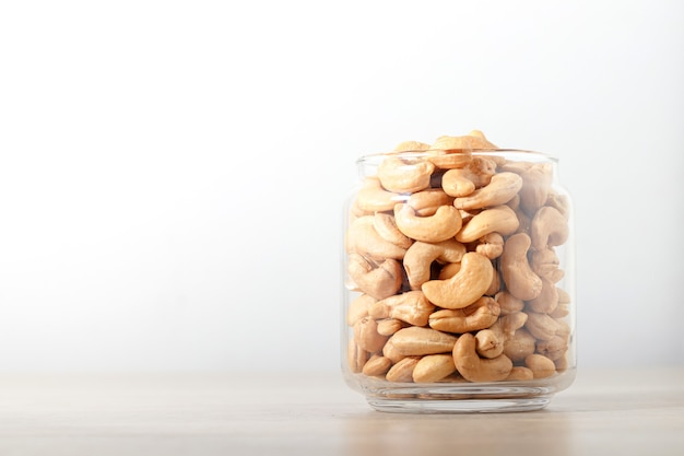 Cashew nuts in glass bottles placed on a wooden floor. food photography concept.