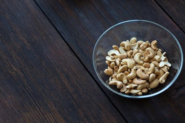 Орехи кешью в тарелке на черном деревянном столе