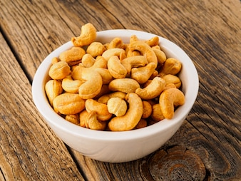 Cashew nuts in  white cup on brown wooden background, side view