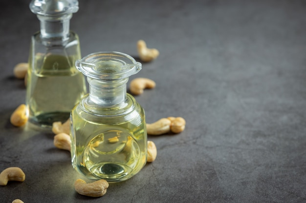 Cashew nuts oil with cashew nuts on dark background