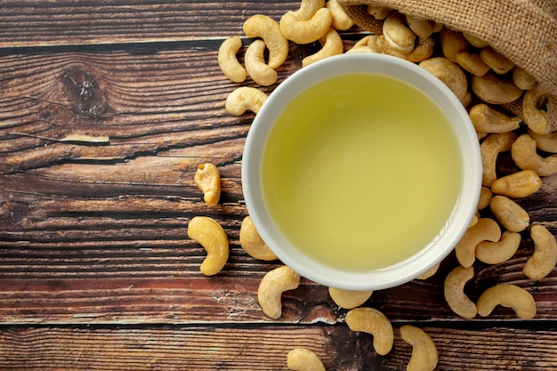 Cashew nuts oil with cashew nuts on dark wood background