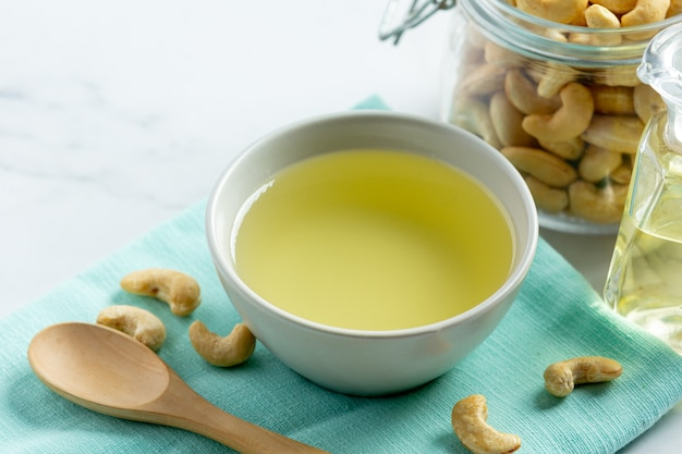 Cashew nuts oil with cashew nuts on marble background