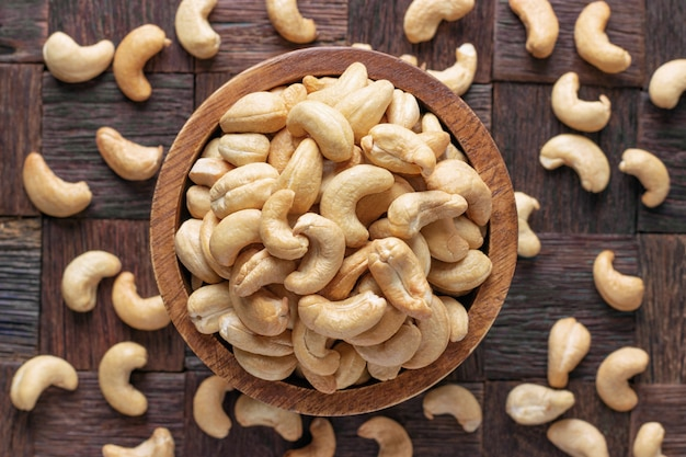 Cashew nuts peeled roasted in wooden bowl, top view.